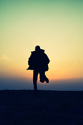 Rear view silhouette of a man running away at sunset  - p794m2073061 by Mohamad Itani