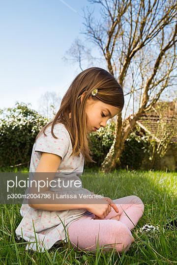 Little girl sitting on a meadow picking daisies - p300m2004796 von Larissa Veronesi