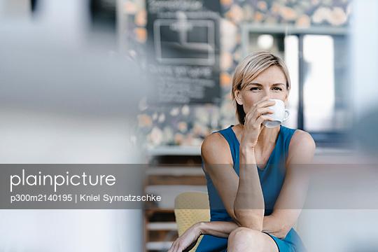 Woman drinking coffee in a coffee shop - p300m2140195 by Kniel Synnatzschke