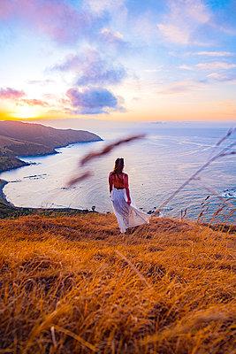 Frau im Abendkleid in weiter Landschaft am Meer - p1455m2203674 von Ingmar Wein