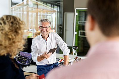 Smiling businessman with digital tablet discussing with colleagues at desk in office - p300m2267108 by Peter Scholl