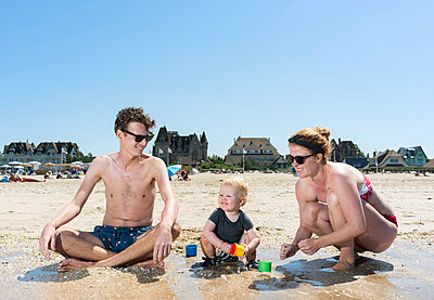 Parents playing with toddler on beach - p429m2019615 by Mischa Keijser