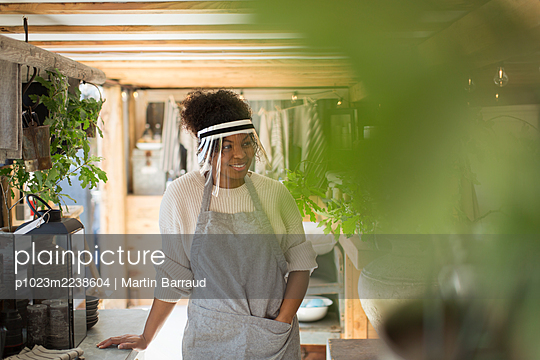 Woman in protective face shield working in plant nursery - p1023m2238604 by Martin Barraud