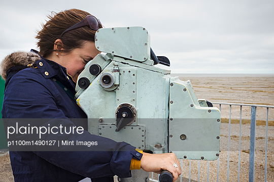 Side view of woman standing on the coast, looking through coin operated binoculars. - p1100m1490127 by Mint Images