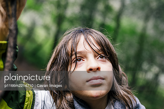 Close up boy looking up with wet hair at forest - p1166m2214710 by Cavan Images