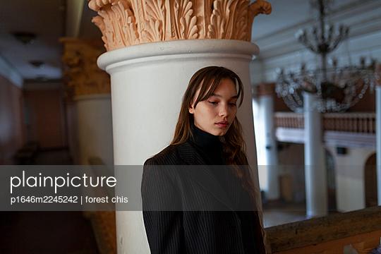 Junge Frau mit langen Haaren lehnt an einer Säule - p1646m2245242 von Slava Chistyakov