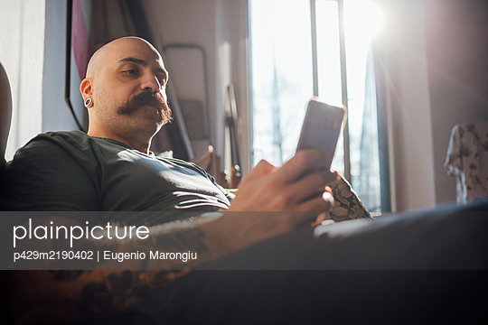 Bald man with moustache lying on sofa, using mobile phone while self isolating during Corona crisis. - p429m2190402 by Eugenio Marongiu