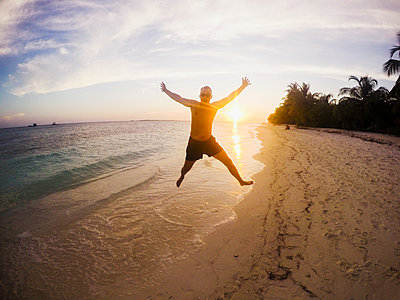 Portrait of exuberant man jumping on tropical beach at sunset - p1023m1156431 by Paul Bradbury