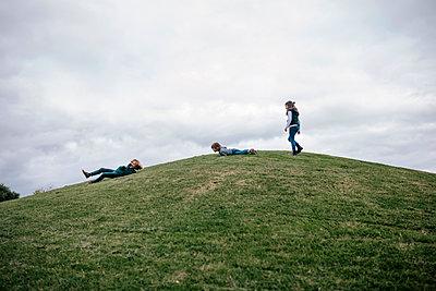 Three children playing on a hill - p300m2160118 von LUPE RODRIGUEZ