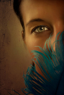 Woman covering face with blue feather - p7940274 by Mohamad Itani
