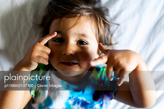 little girl with colorful top lying in bed - p1166m2137300 by Cavan Images