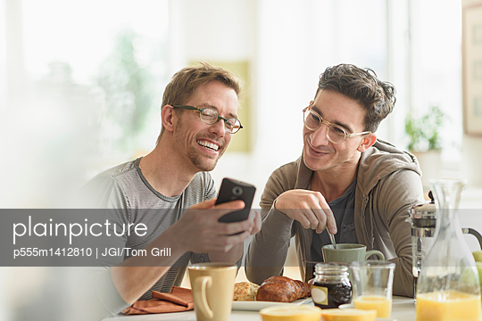 Caucasian gay couple using cell phone at breakfast - p555m1412810 by JGI/Tom Grill
