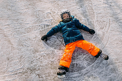 High angle portrait of boy making snow angel - p1166m1568781 by Cavan Images