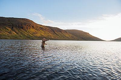 Man fishing in lake - p312m2051307 by Hans Berggren
