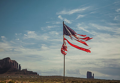 Tattered stars and stripes flag against Monument Valley backdrop, Utah, USA - p924m2023155 by Seb Oliver