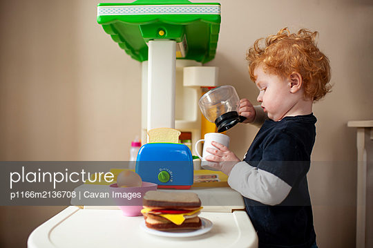 Toddler boy playing in toy kitchen pretending to pour coffee into cup - p1166m2136708 by Cavan Images