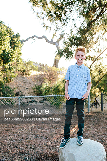 A Red Haired Boy Smiles While Standing On A Large Rock - p1166m2200269 by Cavan Images