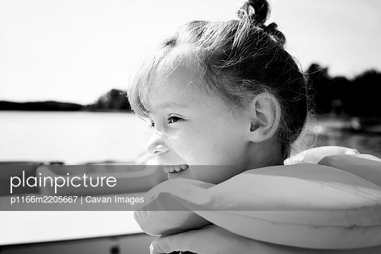 portrait of  young girl sat on a boat in summer - p1166m2205667 by Cavan Images
