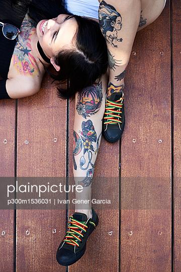 plainpicture | Photo library for authentic images - plainpicture p300m1536031 - Happy woman lying on leg of... - plainpicture/Westend61/Ivan Gener Garcia