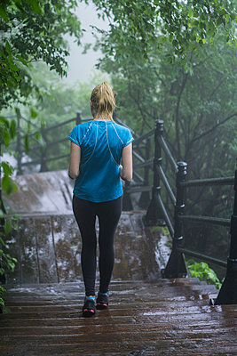 Girl running in the rain - p1362m1227701 by Charles Knox