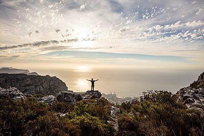 South Africa, Cape Town, Table Mountain, man standing on a rock at sunset - p300m2023511 by Daniel Waschnig Photography