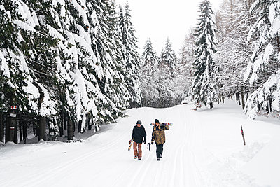 Italy, Modena, Cimone, couple with skiers and snowboard walking in winter forest - p300m2029391 von Juri Pozzi