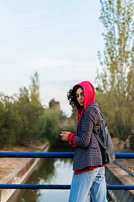 Portrait of young woman with backpack and mobile phone standing on a bridge - p300m2143818 von Eloisa Ramos