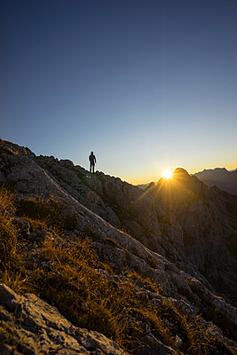 Rear view of hiker standing on viewpoint during sunrise, Gimpel, Tyrol, Austria - p300m2206848 by Matthias Aletsee