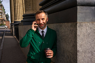 Smiling businessman talking on mobile phone while leaning on pillar of Kazan Cathedral at Saint Petersburg, Russia - p300m2227300 by Vasily Pindyurin
