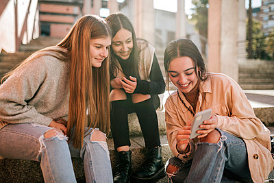 Smiling teenage girl showing mobile phone to friends while sitting on steps in city - p300m2251614 by LUPE RODRIGUEZ