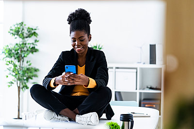 Smiling young Afro female entrepreneur text messaging using smart phone while sitting cross-legged on desk - p300m2251971 by Giorgio Fochesato