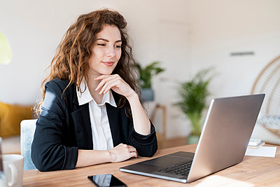 Businesswoman with hand on chin looking at laptop in home office - p300m2276472 by Steve Brookland
