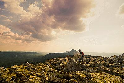 Caucasian hiker walking in rocky field in remote landscape - p555m1411155 by Aleksander Rubtsov