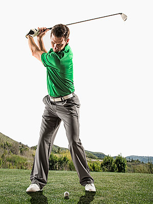 Caucasian man playing golf on course - p555m1420154 by Erik Isakson