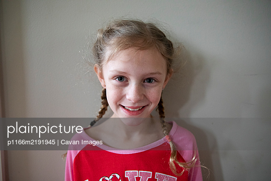 Blonde Girl With French Braids Wearing Pajamas Smiles to Camera - p1166m2191945 by Cavan Images