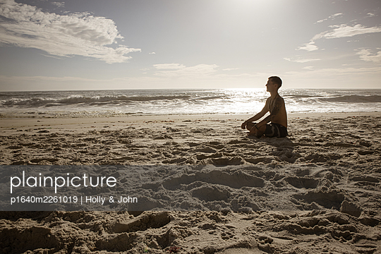 Man practises meditation on the beach at sunset - p1640m2261019 by Holly & John