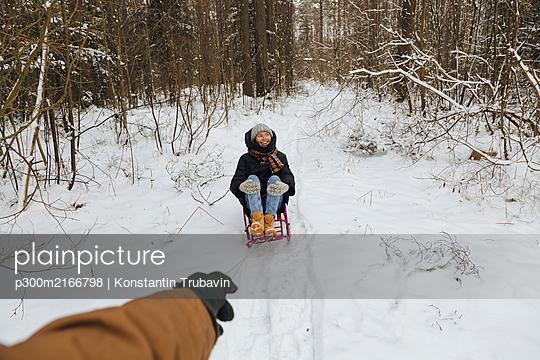 Man's hand pulling woman sitting on a sledge - p300m2166798 by Konstantin Trubavin