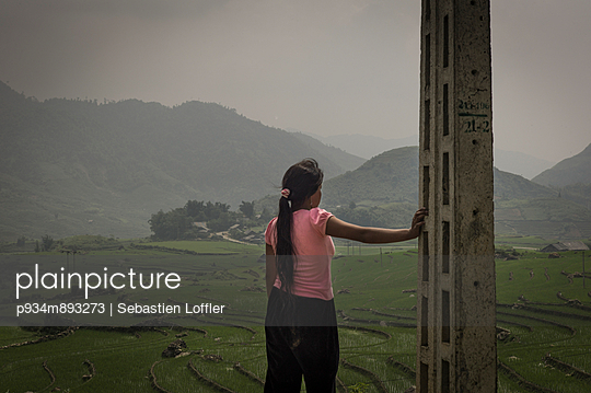 A Vietnamese woman contemplatively looks out over the green valley - p934m893273 by Sebastien Loffler