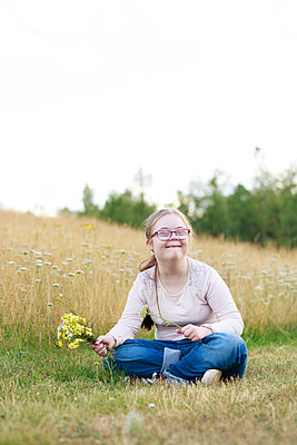 Smiling girl on meadow holding wildflowers - p312m2216991 by Phia Bergdahl