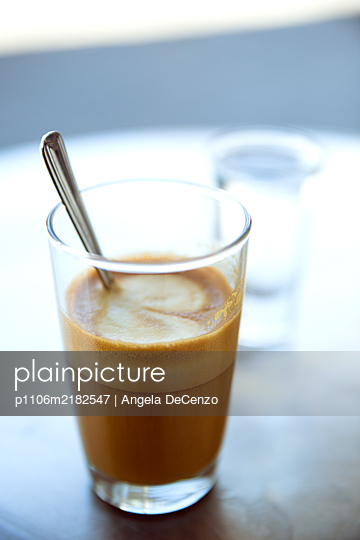 A cortado alongside water glass - p1106m2182547 by Angela DeCenzo