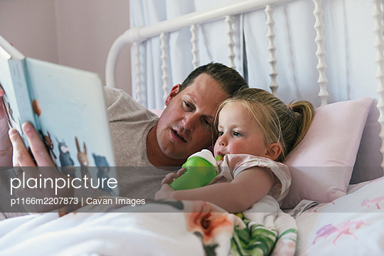 Father and young daughter laying down in bed and reading a book - p1166m2207873 by Cavan Images