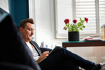 Man sitting in an office using his mobile phone, a vase with red roses on a desk. - p1100m1177694 by Mint Images