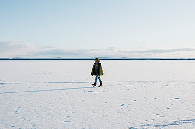 boy walking across a frozen lake alone in Sweden - p1166m2171471 by Cavan Images