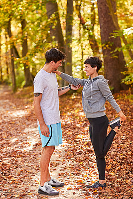 Couple stretching in autumn forest - p300m1581516 by Stefan Hobmaier