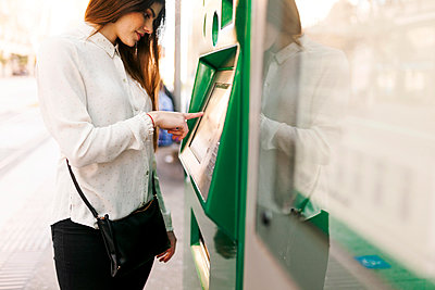 Spain, Barcelona, woman buying ticket from automated machine at  station - p300m1587980 von Valentina Barreto