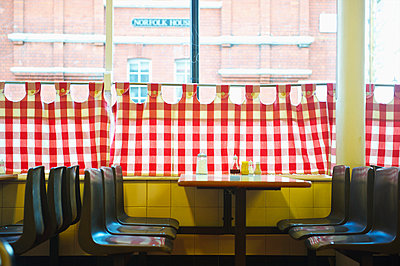 A restaurant with red and white checkered curtains on the window and a yellow wall; London, England - p442m936503 by Ingrid Rasmussen