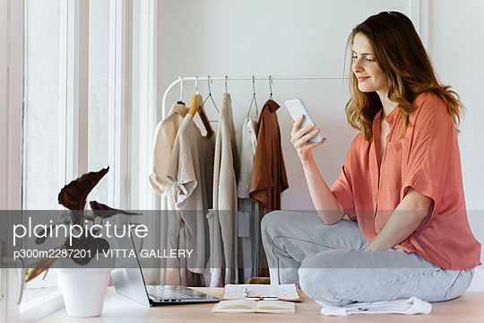 Female entrepreneur using mobile phone while sitting on table at home - p300m2287201 by VITTA GALLERY
