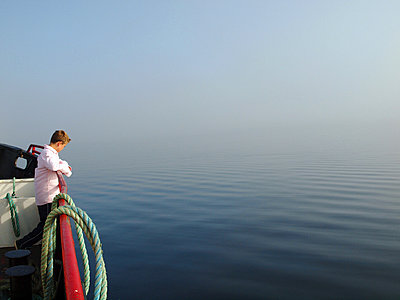 Boy on Tancook ferry looking out to sea in Mahone Bay in Nova Scotia - p1072m828936 by Clive Branson