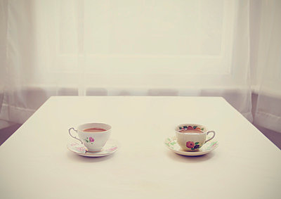 Two teacups on a table - p1072m829367 by Neville Mountford-Hoare