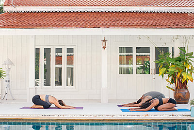 Two women and a man practicing yoga at the poolside - p300m1587084 by Mosu Media